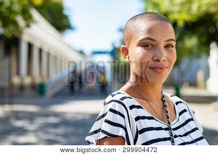 Portrait of young happy bald woman on city street looking at camera. Confident stylish girl outdoor with copy space. Proud and satisfied black curvy woman standing on street.