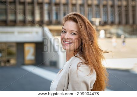 Portrait of beautiful young woman smiling while looking at camera. Mature woman with red hair and freckles looking at camera with big smile. Friendly casaul woman standing on city street feeling.