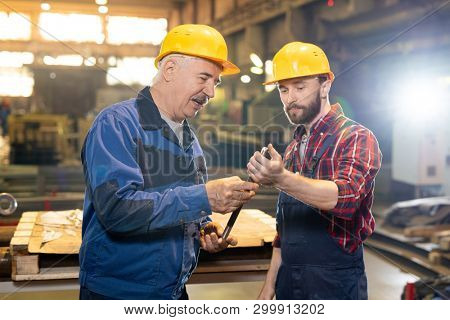 Two confident machinebuilding experts in workwear consulting about usage or features of workpiece in their hands poster