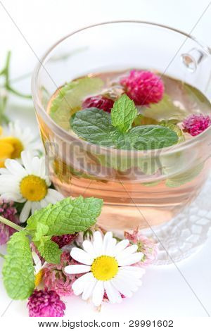cup of herbal tea and fresh flowers close up