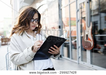 A Young, Sympathetic Woman, Not A Thin-headed Body Building, Holds A Folder Of Paper In Her Hands. H