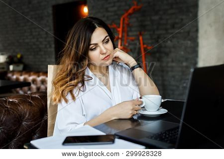A Young, Sympathetic Woman, Not A Thin-headed Body Building, Sits In A Cozy Cafe, Works On A Compute