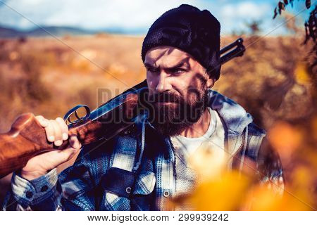 Poacher In The Forest. Bearded Hunter Man Holding Gun And Walking In Forest. Hunting Licenses. Hunte