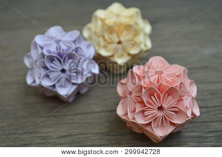 Purple, Yellow And Pink Origami Kusudama Flower On Wooden Background