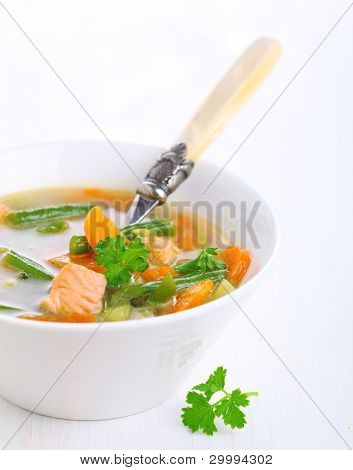 Vegetable soup with salmon in white bowl