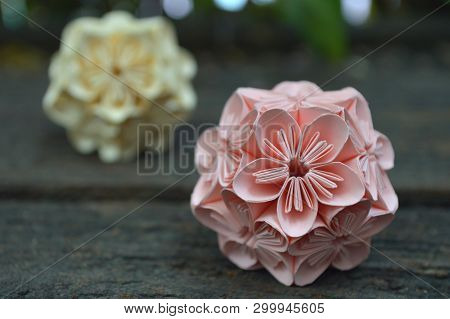 Yellow And Pink Origami Kusudama Flower On Wooden Background