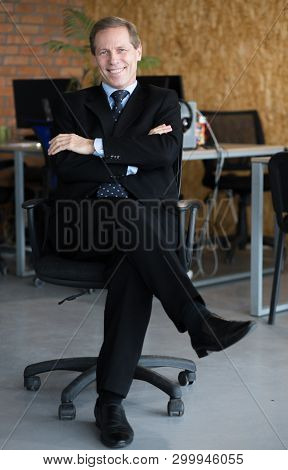 Happy Young Business Man With Hands Crossed Sitting On A Chair And Smiling With A Wide Bright Smile.