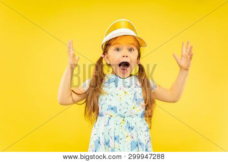 Beautiful Emotional Little Girl Isolated On Yellow Background. Half-lenght Portrait Of Happy And Ast