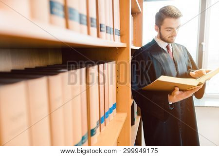 Lawyer with robe ready for court reading after the law one last time in the library of the firm