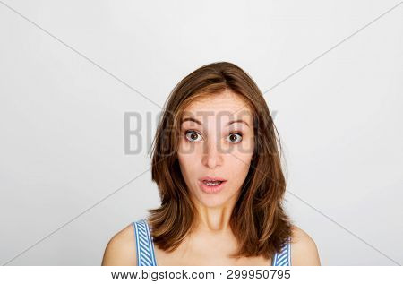 Amazed young woman looking at camera on white background.