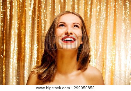 Blond woman standing on gold sequins background. New year concept.
