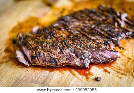 Sliced Grilled Juicy Marinated Beef Flank Steak On Wooden Board.