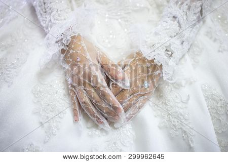 Woman In White Wedding Dress, Bride Hands In White Bride Gloves. Traditional Islamic Hijab Wedding D