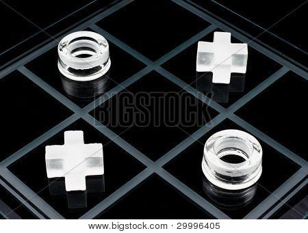 Glass tic-tac-toe game on black background