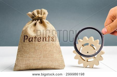 Money Bag With The Word Patents And A Wooden Gear. Registration Of Patents And Copyright Compliance.