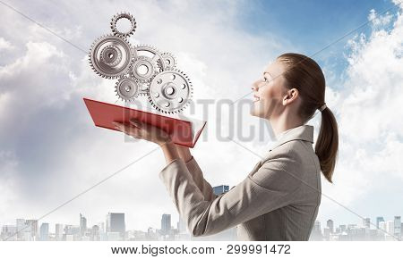 Woman Holding Open Notebook With Flying Abstract Mechanism With Cogwheels. Construction And Manufact