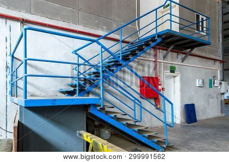 Blue Metal Ladder In An Old Factory. Red Fire Box And Fire Tube On The Wall.