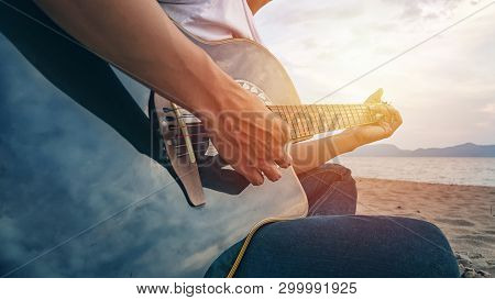 Man's Hands Playing Acoustic Guitar, Capture Chords By Finger On Sandy Beach At Sunset Time. Playing