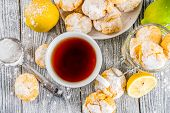 Lemon Crinkle Cookies, homemade sweet and sour baking with tea cup, white wooden background copy space poster