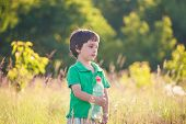 The child drinks water from a plastic bottle. The boy quenches thirst. The kid is holding a bottle of water on the background of green grass. Walk in nature. poster