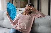 Woman feels discomfort from heat waving blue fan to cool poster