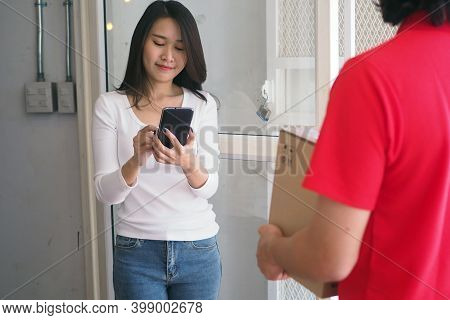 Good Tempered Woman Signed On The Smartphone To Receive Parcels From The Sender. Fastest Online Deli