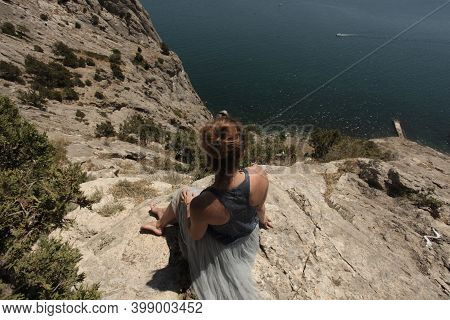 The Girl Sits On The Edge Of A Cliff And Looks Out To Sea. Meditation In The Fresh Air.