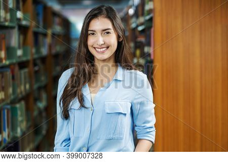 Portrait Of Asian Young Student In Casual Suit  In Library Of University Or College Over Book Shelf