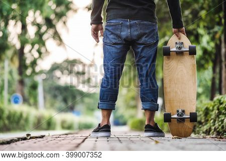 Closeup Asian Man Holding Surfskate Or Skate Board In Outdoor Park When Sunrise Time Over Photo Blur