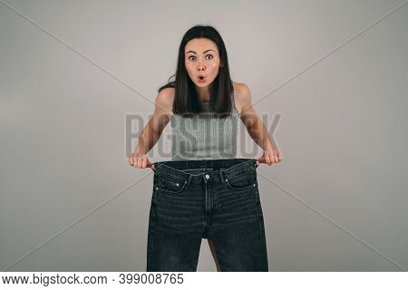 The Girl Lost A Lot Of Weight. The Girl Is Holding Very Large Jeans. The Woman Is Surprised How She