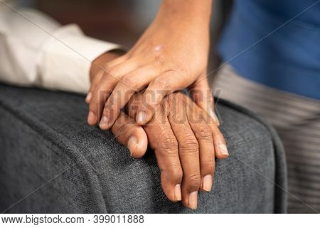 Close Up Of Doctor Hands Holding Hand Of A Senior Citizen With Condolence - Concept Of Philanthropy,