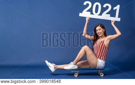 Happy Young Asian Woman Sitting On Surfskate Or Skateboard And Holding 21 2021 White Paper Banner Fo