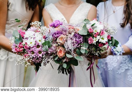 The Bride And Bridesmaids In An Elegant Dress Is Standing And Holding Hand Bouquets Of Pastel Pink F