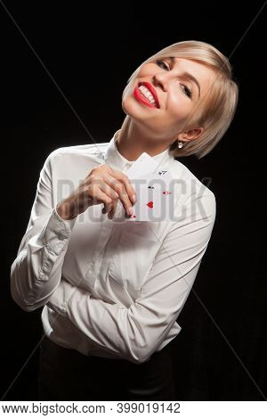 Beautiful Blond Woman Showing A Poker Cards On Black Background