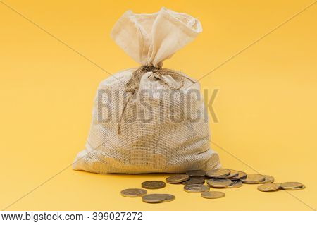 On A Yellow Background A Closed And Knotted Bag With Money, Several Coins Nearby. Concept - Saving M