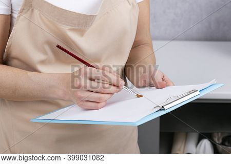 Woman Holds Sheet Of Paper And Paintbrush. Close Up.