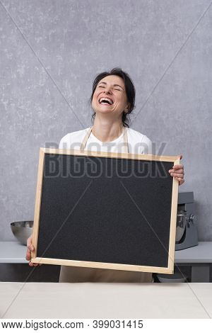 Woman Holds Chalk Board In Her Hands And Laughs. Copy Space, Mock Up. Vertical Frame.