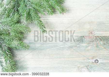 Christmas background. Winter Christmas background. Green fir tree branches with Christmas winter snowflakes on the wooden background. Christmas winter border with free space for text