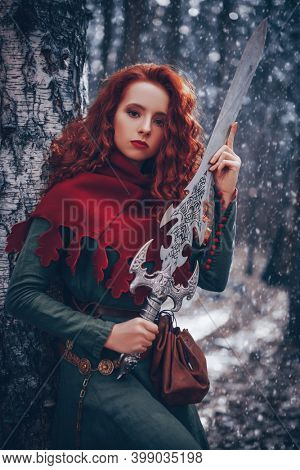 Ancient legends. A beautiful warrior woman with a sword in a deep winter forest. Fantasy world.