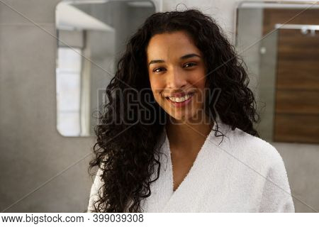Portrait of mixed race woman in bathroom smiling to camera. looking at the camera and smiling. self isolation at home during covid 19 coronavirus pandemic.
