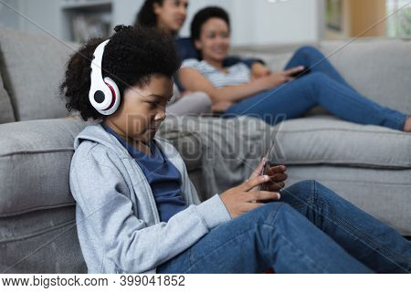 Mixed race girl sitting by couch listening to music. self isolation quality family time at home together during coronavirus covid 19 pandemic.
