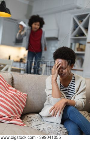 Mixed race woman sitting on couch holding her forehead. self isolation quality family time at home together during coronavirus covid 19 pandemic.