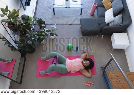 Overhead view of african american woman lying on exercise mat working out. self isolation fitness at home during coronavirus covid 19 pandemic.