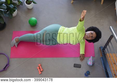 High angle view of african american woman lying on exercise mat working out. self isolation fitness at home during coronavirus covid 19 pandemic.