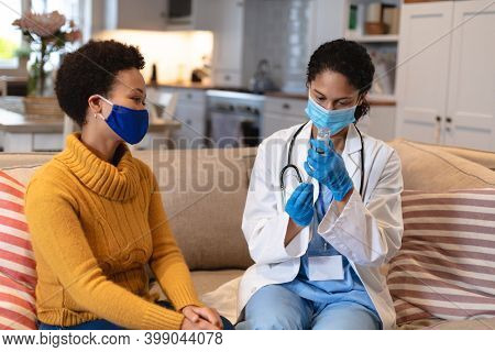 Mixed race woman wearing face mask talking to a mixed race female doctor sitting on couch. self isolation at home together during coronavirus covid 19 pandemic.