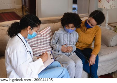 Mixed race mother and daughter talking to mixed race female doctor sitting on couch. self isolation at home together during coronavirus covid 19 pandemic.