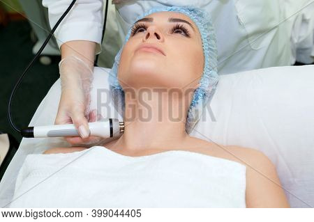 A Young Woman Is Lying On The Rf-lifting Procedure For Face Skin Tightening And Face Contour Correct