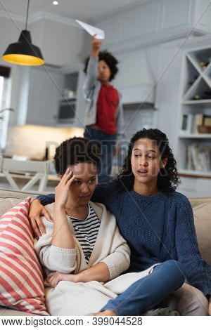Mixed race lesbian couple sitting on couch talking. self isolation quality family time at home together during coronavirus covid 19 pandemic.