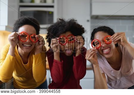 Portrait of mixed race lesboan couple and daughter having fun with food in kitchen. self isolation quality family time at home together during coronavirus covid 19 pandemic.