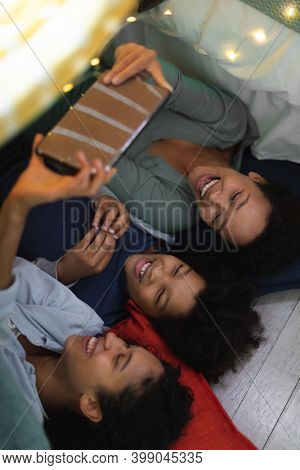 Happy mixed race lesbian couple and daughter lying down using smartphone. self isolation quality family time at home together during coronavirus covid 19 pandemic.